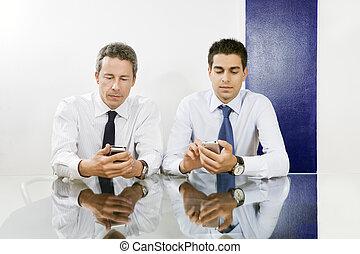 Two businessmen checking blackberries in meeting room.