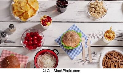 Burger and bowl of pickles. Fast food with fresh vegetables....