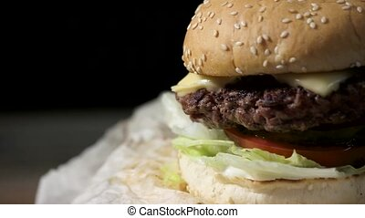 Burger close-up on black background. Grilled meat and...