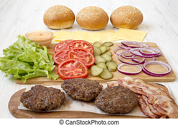 Burger ingredients on a white wooden background, side view. Close-up.