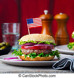 Burger on a plate with American flag. Wooden background.
