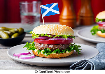 Burger on a plate with pickles. Wooden background. - Burger...