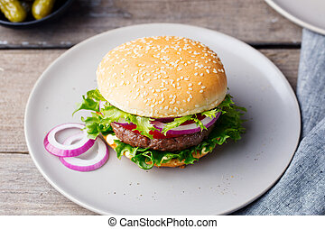 Burger on a plate with pickles. Wooden background.