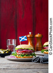 Burger on a plate with pickles. Wooden background. Copy space.