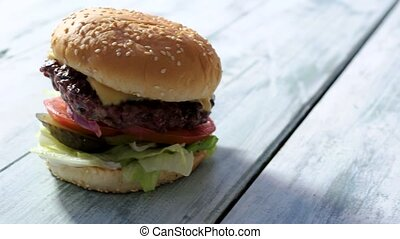 Burger on gray wooden surface. Side view of a hamburger....