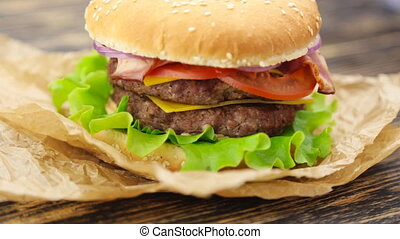 Burger on wooden table - Bacon burger with beef patty on...