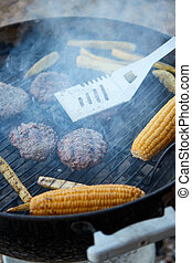 Burger patties and corn on a hot barbecue grill