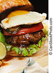 Burger with egg on a wooden board closeup