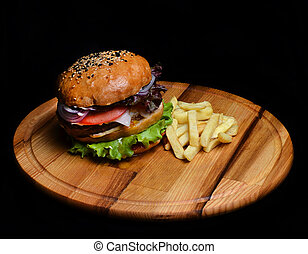 Burger with French fries on a wooden board. Fast food.