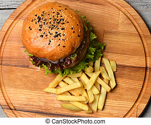 Burger with French fries on a wooden board. Top view. Fast food.