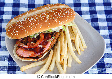 Burger with fries and tomato ketchup on a blue checkered tablecloth