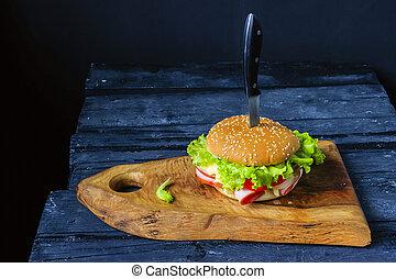 Burger with ham on a cutting board knife pierced