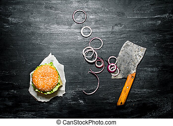 Burger with onion rings and an old hatchet. On a black chalkboard. Top view.