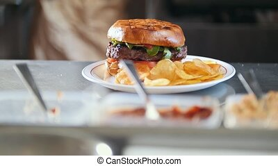 Burger with potato chips on a plate in restaurant kitchen