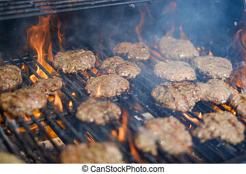 burgers on grill , flaming barbecue gril with hamburgers
