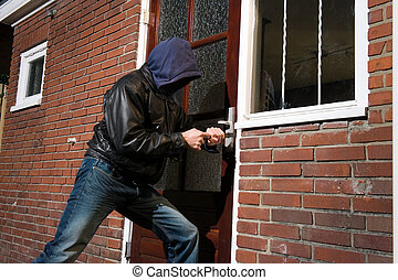 A burglar trying to get into a house by the backdoor