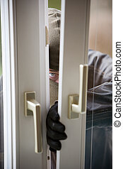 Burglar at a window - A burglar at a window of a house.