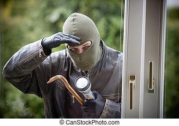 a burglar breaking in the window of a house