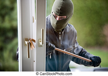 burglar at a window - a burglar breaking in the window of a...
