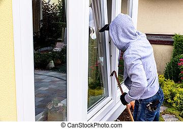 burglar at a window - a burglar tries to break in at an open...