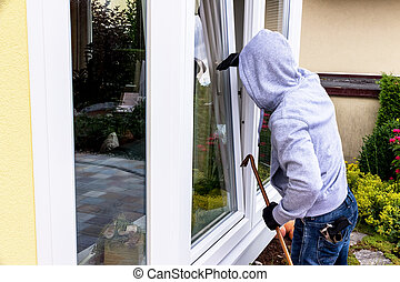 burglar at a window - a burglar tries to break in at an open...