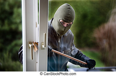 Burglar at a window - A burglar at a window of a house.