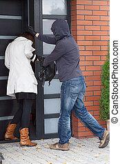Burglar attacking a woman