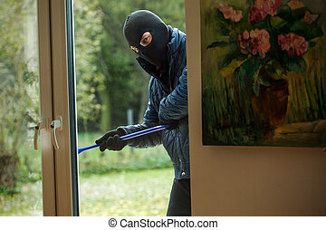 Burglar behind window - A burglar observing the house from...