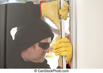 Burglar breaking through window of house - Male burglar with...