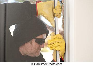 Burglar breaking through window of house - Male burglar with...