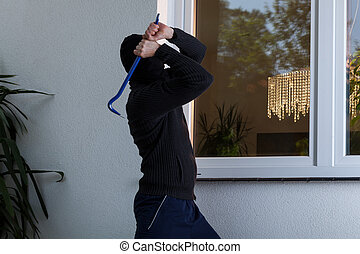 Burglar breaks the window - Burglar with obscured face ...