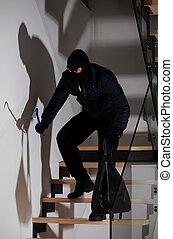Burglar creeping on stairs
