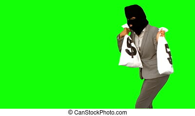 Burglar holding money bags on green screen in slow motion