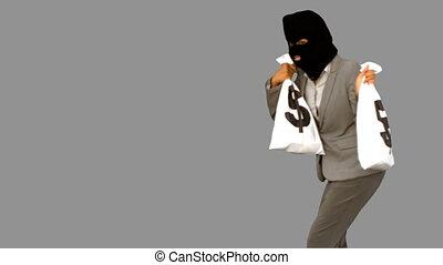 Burglar holding money bags on grey screen in slow motion