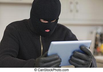 Burglar holding tablet pc