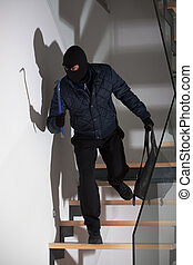 Burglar laying in wait - A masked burglar lying in wait for ...