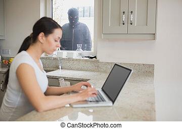 Burglar observing woman in the kitchen