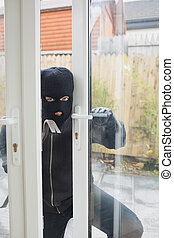 Burglar opening carefully the door