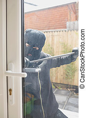 Burglar opening door with crow bar