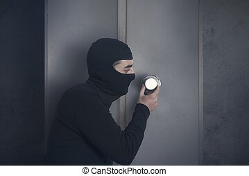 Burglar opening strongbox - Concept of burglar that open a...