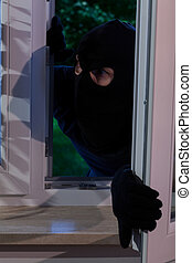 Burglar opening the window - Vertical view of burglar...