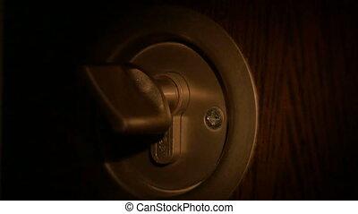 Burglar Opens Lock - Thief with flashlight in darkness in...