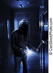 Burglar with flashlight and crow bar in a dark office...