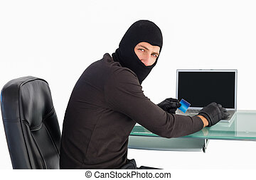 Burglar shopping online with laptop while looking at camera ...