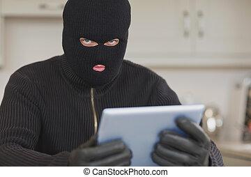 Burglar stealing the tablet pc