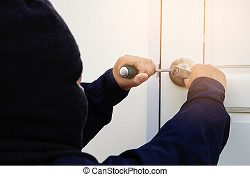 Burglar trying to break into a house with screwdriver.