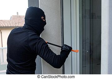 Burglar trying to force a door lock using crowbar