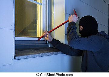 Burglar Using Crowbar To Break Into A House