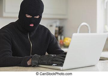 Burglar using laptop
