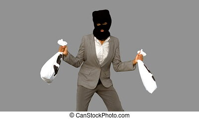 Burglar wearing balaclava and holding money bags on grey...